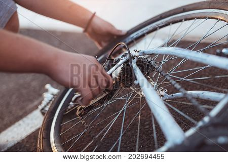 Teenager boy repair tire on bicycle summer outdoor photo close up