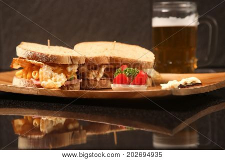 Sandwiches on a wooden plate with a beer on the table