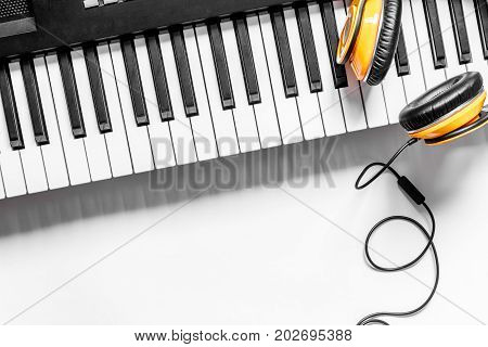 Desk of musician for songwriter work set with headphones and synthesizer on white background top view mockup