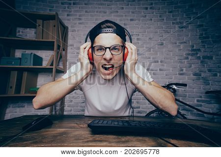 Young man holding his red headphones with both hands and playing game at home and streaming playthrough or walkthrough video. Handsome guy is screaming because of win in vr. Looking at camera