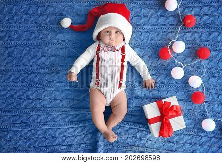 Cute little baby in Santa hat with gift box and garland on knitted fabric