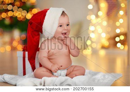Cute little baby in Santa hat sitting on floor against blurred Christmas lights