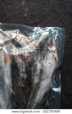 Frozen smelt in vacuum packing on a beige background vertical