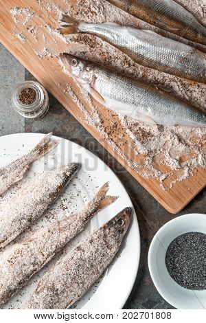 Smelt on a plate and on a cutting board vertical