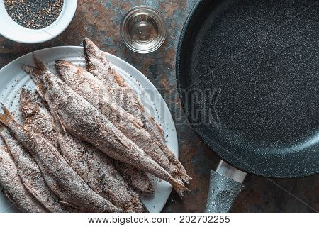 Smelt on a plate, frying pan, salt and spices close-up horizontal