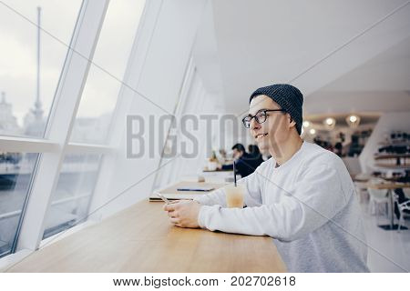 Man is sitting in front of the table near window. Smiling young student has time break. He is looking through window and waiting for his friends