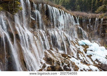 Waterfall in the forest. Frozen water drains over the rocks. The rock is covered with moss on which cold water flows.The flow of water from the rocks