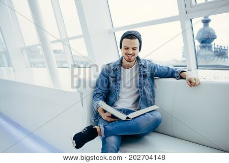 young, successful business man sitting in cafe with book on sofa. Smiling student is reading interesting articles during coffeebreak