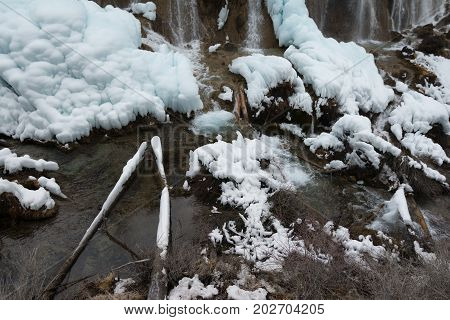 Waterfall in the forest. Frozen water drains over the rocks. The rock is covered with moss on which cold water flows.Waterfall on a rock. Frozen water on a rock