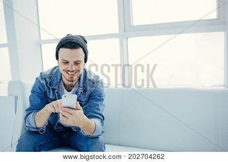 young man sitting in cafe with phone on sofa. Happy student is watching video or serching for informaion and smiling at