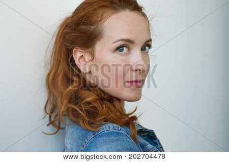 Close up view of beautiful Caucasian woman with ginger hair and freckles looking and smiling at camera at white studio wall. Concept of mature adult emotion