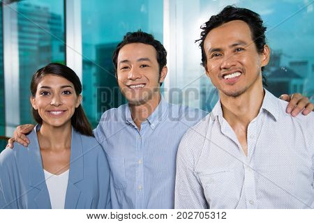 Ambitious business colleagues smiling at camera and standing in corridor. Cheerful Asian businessman embracing colleagues and enjoying their partnership. Startup company concept