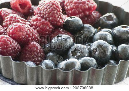 Blueberries and Raspberries in the black vintage metal bowl on a rustic wooden board