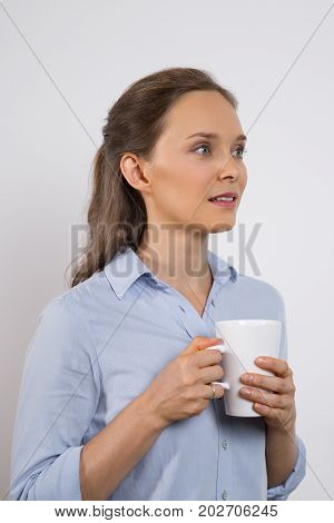 Dreamy beautiful girl holding mug and looking away. Pensive pretty young student thinking of future. Ambitious attractive businesswoman contemplating. Contemplative office worker concept