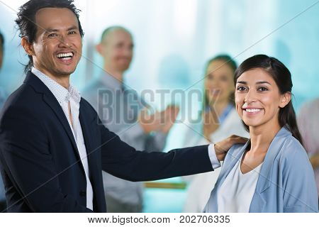 Excited boss congratulating employee with promotion. Cheerful business colleagues looking at camera in office, business people applauding in background. Career in large company concept