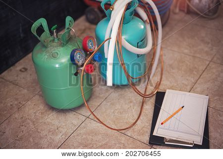 Freon gas balloons with pressure meter. Workshop for replacement of freons in air conditioners