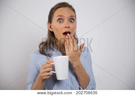 Excited businesswoman with mug shocked with news and looking at camera. Surprised young female employee holding mug and covering open mouth with hand. Shocked news concept