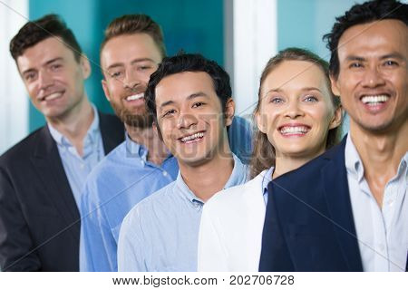 Excited happy business colleagues standing in line and looking at camera. Cheerful Asian businessman enjoying work in well-organized company. Human recourses concept