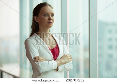 Aspirated confident young businesswoman looking forward. Serious beautiful female manager in jacket crossing arms on chest and standing in corridor. Career concept