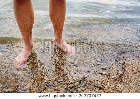 Close Up Background Of Man's Feet Standing In A Clear Water With Pebble Bottom