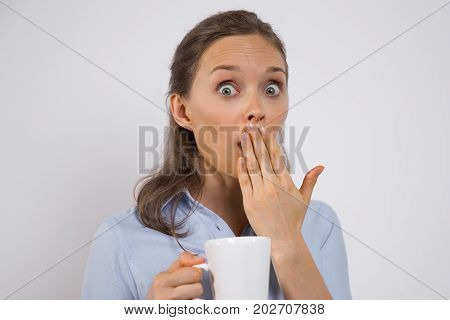 Shocked woman finding out secret of company and looking with surprise at camera. Emotional young businesswoman knowing private information or big sales over coffee. Amazement concept