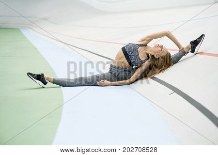 Charming girl with closed eyes sits on the twine on the cycle track outdoors. She holds her right hand on the left leg and presses the torso to it. Girl wears a gray sportswear and dark sneakers.