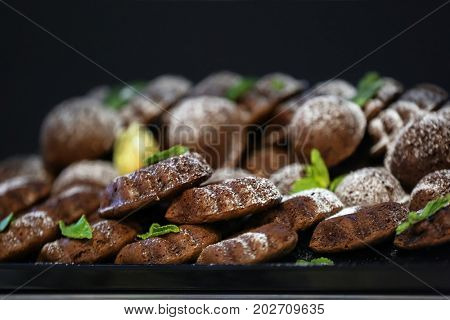 Many chocolate sponge cakes with powdered sugar, closeup