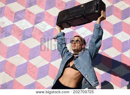 From below shot of slim trendy youngster in sunglasses posing with black boombox on street.
