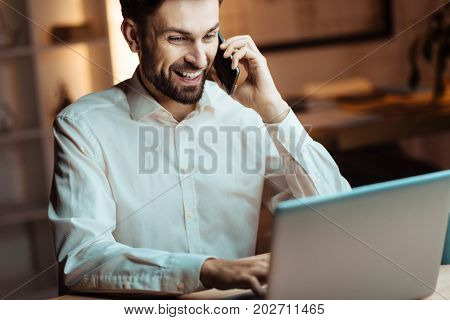 Online conversation. Happy smiling man sitting in semi position and leaning elbows on table while watching video