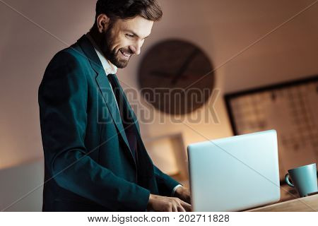 Work with pleasure. Handsome man keeping smile on his face and sitting on the table in semi position while looking at computer