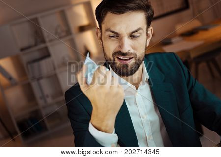 It is boring. Young businessman opening his mouth and raising eyebrows while holding paper ball in right hand