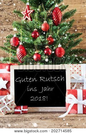 Colorful Christmas With Tree With Balls And Snowflakes. Gifts Or Presents In The Front Of Wooden Background. Chalkboard With German Text Guten Rutsch Ins Jahr 2018 Means New Year 2018