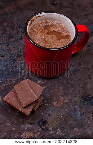 Hot chocolate in mug with chocolate on grunge dark table