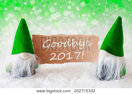 Christmas Greeting Card With Two Green Gnomes. Sparkling Bokeh And Natural Background With Snow. English Text Goodbye 2017