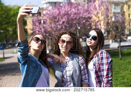 Happy teenage girls doing selfie, hawing fun spend time together in the city park