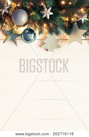White Wooden Background With Copy Space. Vertical Christmas Banner With Turquoise Christmas Decoration Like Balls, Tree And Star. Fir Branches With Fairy Lights And Instagram Filter.