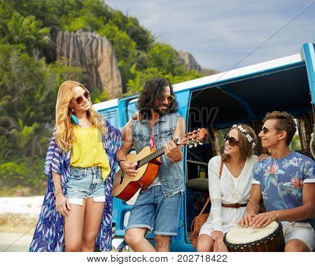 summer holidays, road trip, travel and people concept - happy young hippie friends with guitar and drum playing music at minivan car over island beach background