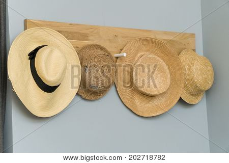 four hats hanging in a wooden wall.