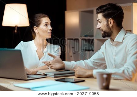 I told you earlier. Delighted man talking to his partner and actively gesticulating while sitting opposite his colleague