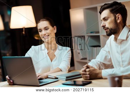Lets chat. Attractive man holding hands together and sitting in semi position while being ready to discuss some points