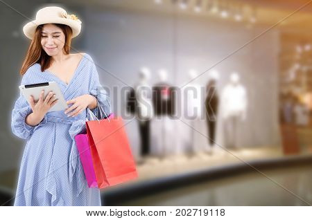 cheerful asian young woman holding shopping bags and mobile tablet while standing at the clothing store in department store shopping mall online payment shopping online lifestyle technology concept