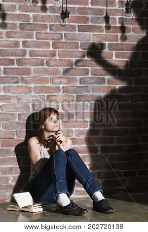 Caucasian girl sitting on the floor reading a horror or scary thriller book. Dramatic lighting with girls eyes wide open and long shadows of woman with knife on the wall near her. Afraid lady looking to somebody. Terrified expression