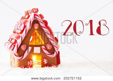 Gingerbread House In Snowy Scenery As Christmas Decoration With White Background. Candlelight For Romantic Atmosphere. Text 2018 For Happy New Year