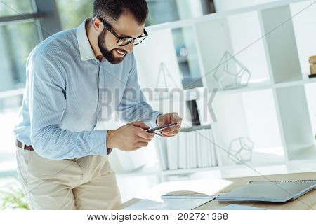 Enabling technologies. Upbeat young man taking photos of printouts lying on his working table in the office while smiling pleasantly