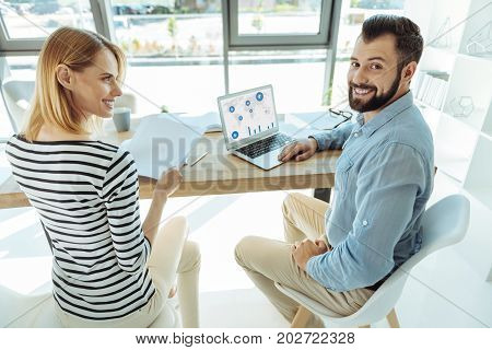 Friendly ambience. Cheerful young man and his charming female colleague creating a presentation while the woman holding documents and the man smiling at the camera