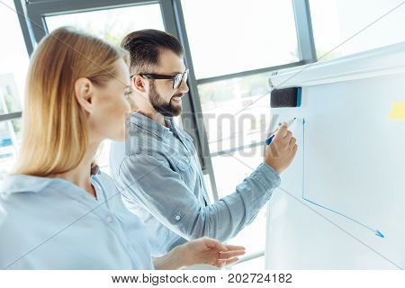 Helpful visualization. Handsome bearded young man drawing a graph of sales on the whiteboard in the office while his female colleague helping him