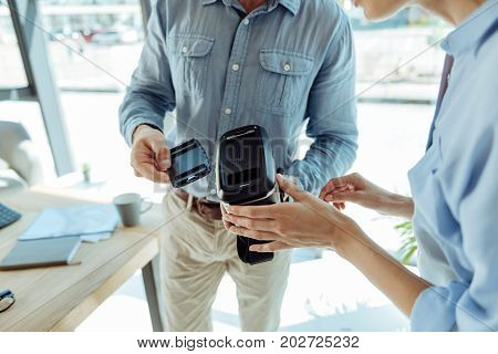 Necessary adjustment. Two office workers holding a VR headset and removing focal distance adjustment from it