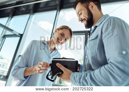 Thorough examination. Two charming office workers holding a virtual reality headset and scrutinizing it from all sides