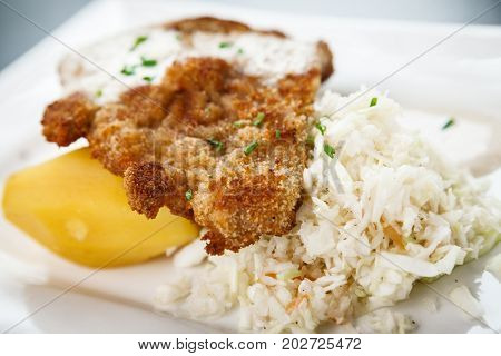 Traditional viennese Schnitzel with potato salad and rice on a withe plate