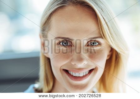 Breathtaking beauty. The portrait of a charming fair-haired blue-eyed woman looking at the camera and smiling broadly
